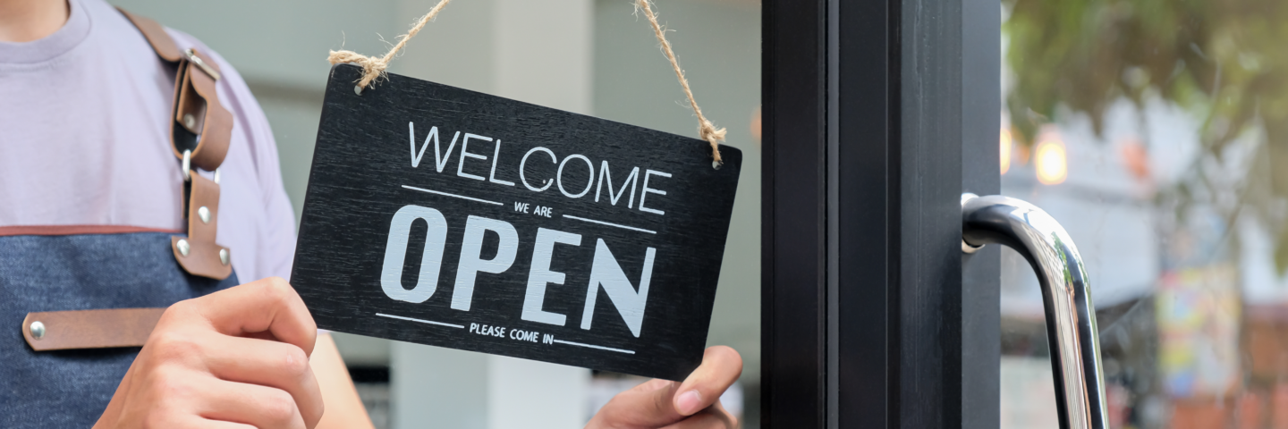 Woman business owner turning 'Business Open' sign on door