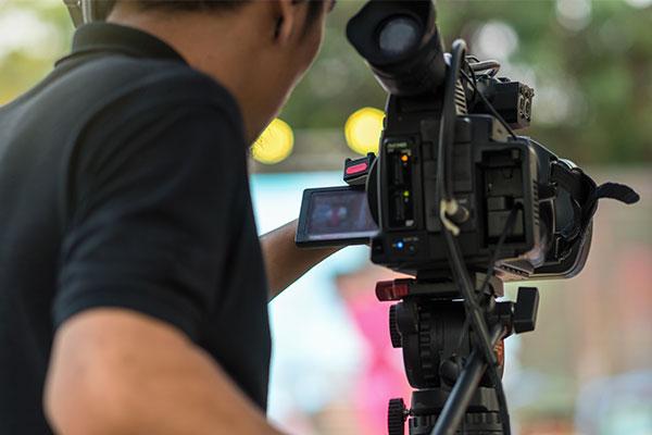 Videographer behind camera filming video shots